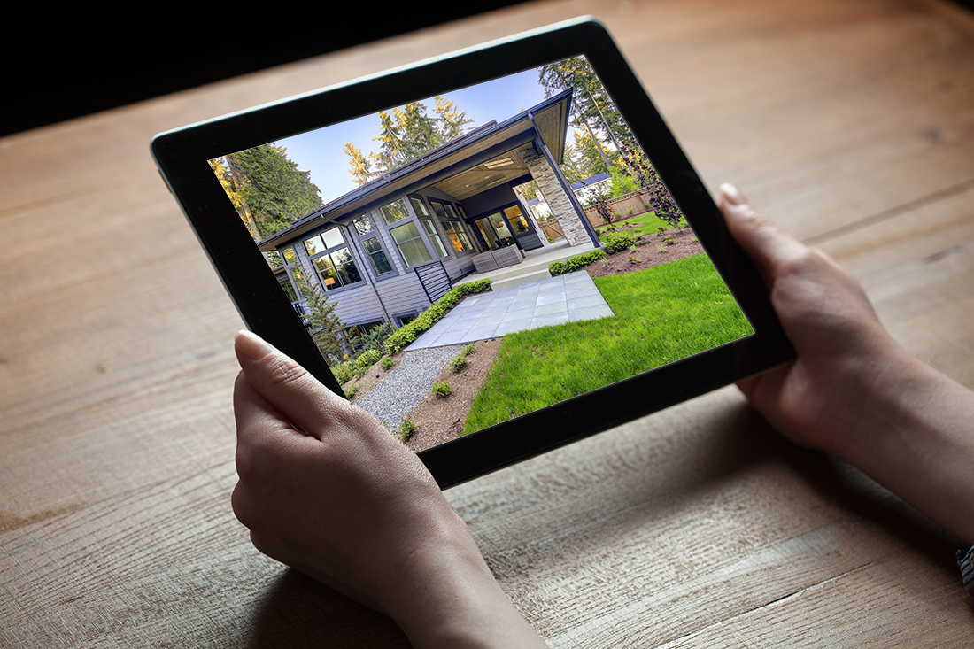 Hands holding digital tablet computer showing a New Modern House with isolated screen over old grey wooden background table
